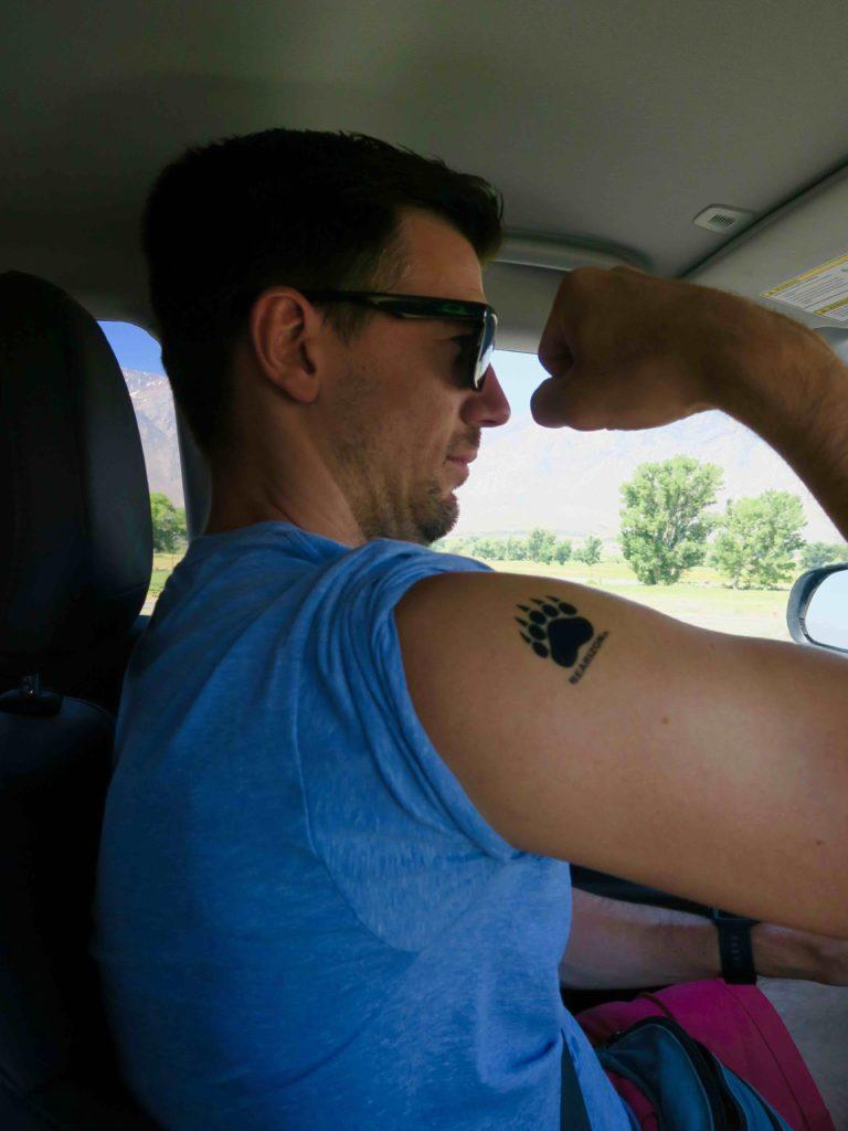 loulou dans la voiture avec un tatouage sur le bras droit