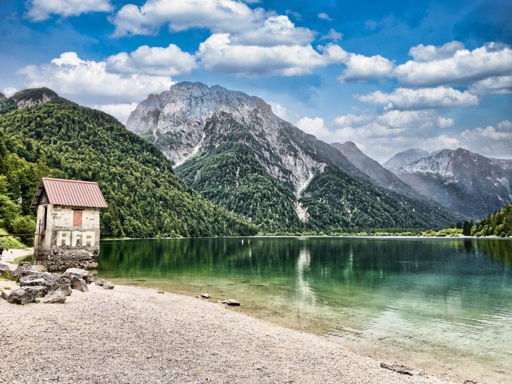Vue de la plage du lac de predil par une journée très ensoleillée. Le reflet des montagnes dans l'eau donne l'effet d'une carte postale.